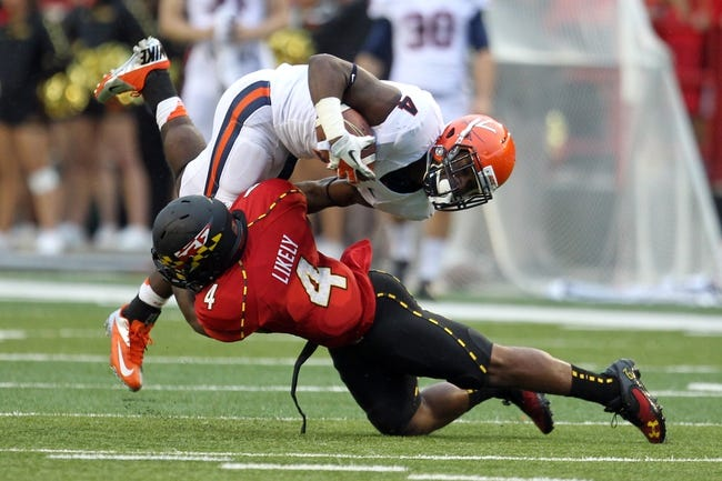 Oct 12, 2013; College Park, MD, USA; Maryland Terrapins defensive back William Likely (4) tackles Virginia Cavaliers tailback Taquan Mizell (4) following a run at Byrd Stadium. Mandatory Credit: Mitch Stringer-USA TODAY Sports