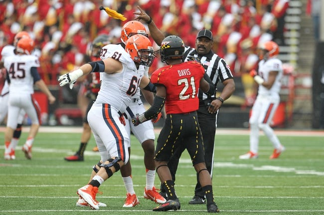 Oct 12, 2013; College Park, MD, USA; Virginia Cavaliers tackle Cody Wallace (61) and Maryland Terrapins defensive back Sean Davis (21) draw a flag after shoving each other during the game at Byrd Stadium. Mandatory Credit: Mitch Stringer-USA TODAY Sports