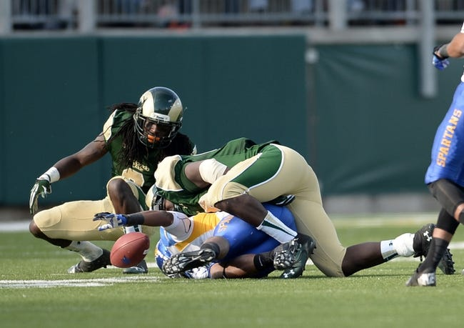 Oct 12, 2013; Fort Collins, CO, USA; San Jose State Spartans wide receiver Thomas Tucker (3) fumbles as he is injured on this play after being tackled by Colorado State Rams linebacker Shaquil Barrett (56) and cornerback Shaq Bell (3) in the second quarter at Hughes Stadium. The Spartans defeated the Rams 34-27. Mandatory Credit: Ron Chenoy-USA TODAY Sports