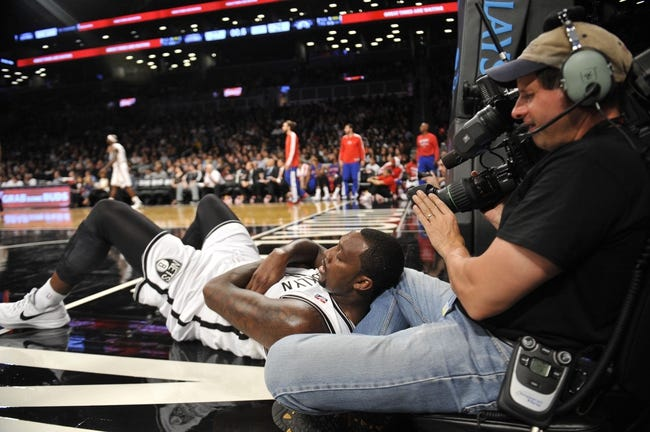 Oct 12, 2013; Brooklyn, NY, USA; Brooklyn Nets power forward Andray Blatche (0) lies on a camera man's legs during the first half of the preseason game against the Detroit Pistons at Barclays Center. Mandatory Credit: Joe Camporeale-USA TODAY Sports