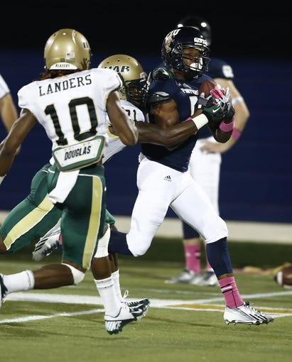 Oct 12, 2013; Miami, FL, USA;  Florida International Panthers wide receiver Clinton Taylor (5) catches a pass while being defended by Alabama-Birmingham Blazers cornerback Kelton Brackett (back) and cornerback Vashon Landers (10) in the second quarter at FIU Stadium. Mandatory Credit: Robert Mayer-USA TODAY Sports