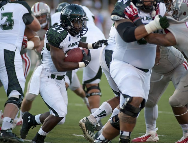 Oct 12, 2013; Las Vegas, NV, USA; Hawaii Rainbow Warriors running back Diocemy Saint Juste looks for a seam along the UNLV Rebels line during an NCAA football game at Sam Boyd Stadium. Mandatory Credit: Stephen R. Sylvanie-USA TODAY Sports