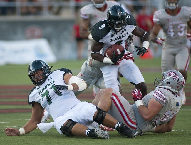 Oct 12, 2013; Las Vegas, NV, USA; Hawaii Rainbow Warriors wide receiver Chris Gant (9) gets wrapped up after making a short reception against the UNLV Rebels during an NCAA football game at Sam Boyd Stadium. Mandatory Credit: Stephen R. Sylvanie-USA TODAY Sports