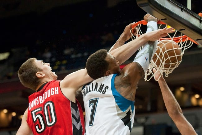 Oct 12, 2013; Minneapolis, MN, USA; Minnesota Timberwolves power forward Derrick Williams (7) dunks while defended by Toronto Raptors power forward Tyler Hansbrough (50) in the second quarter at Target Center. Raptors won 104-97. Mandatory Credit: Greg Smith-USA TODAY Sports