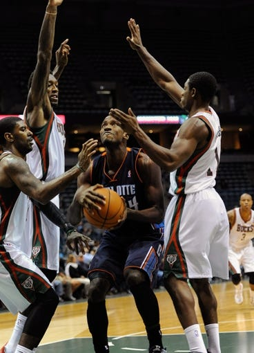 Oct 12, 2013; Milwaukee, WI, USA;  Charlotte Bobcats forward Michael Kidd-Gilchrist (14) is defended by Milwaukee Bucks guard O.J. Mayo (0), center Larry Sanders (8) and guard Brandon Knight (11) in the 3rd period at BMO Harris Bradley Center. Mandatory Credit: Benny Sieu-USA TODAY Sports