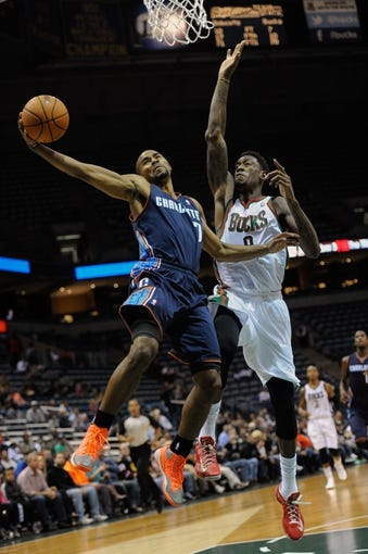 Oct 12, 2013; Milwaukee, WI, USA;  Charlotte Bobcats guard Ramon Sessions (7) takes a layup against Milwaukee Bucks center Larry Sanders (8) in the 3rd period at BMO Harris Bradley Center. Mandatory Credit: Benny Sieu-USA TODAY Sports