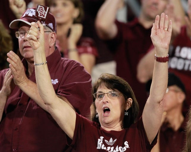 Oct 12, 2013; Starkville, MS, USA; Mississippi State Bulldogs fan cheers her team on late in the game against the Bowling Green Falcons at Davis Wade Stadium. The Bulldogs defeated the Falcons 21-20. Mandatory Credit: Marvin Gentry-USA TODAY Sports