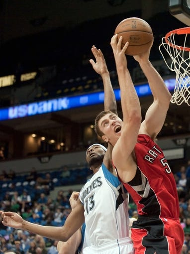 Oct 12, 2013; Minneapolis, MN, USA; Toronto Raptors power forward Tyler Hansbrough (50) rebounds against Minnesota Timberwolves small forward Corey Brewer (13) in the second quarter at Target Center. Raptors won 104-97. Mandatory Credit: Greg Smith-USA TODAY Sports