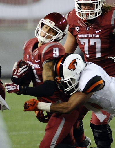 Oct 12, 2013; Pullman, WA, USA; Washington State Cougars wide receiver Gabe Marks (9) is tackled by Oregon State Beavers cornerback Sean Martin (6) during the first half at Martin Stadium. Mandatory Credit: James Snook-USA TODAY Sports