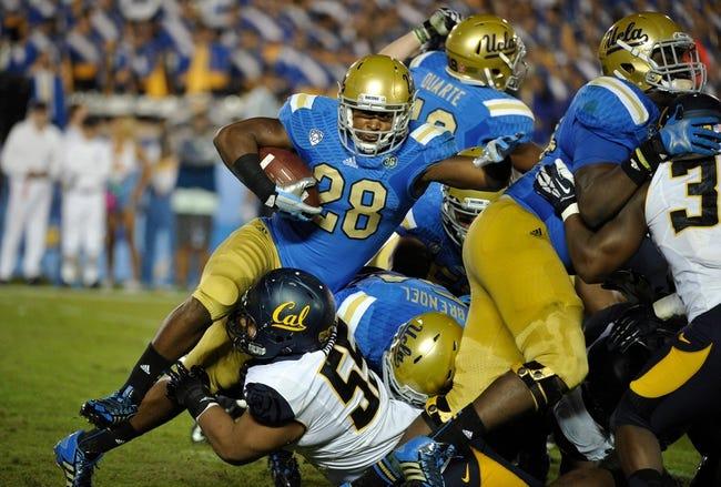 Oct 12, 2013; Pasadena, CA, USA; UCLA Bruins running back Malcolm Jones (28) is tripped up by California Golden Bears defensive lineman Viliami Moala (55) near the goal line during fourth quarter action at Rose Bowl. Mandatory Credit: Robert Hanashiro-USA TODAY Sports