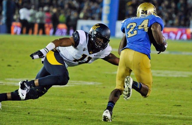 Oct 12, 2013; Pasadena, CA, USA; California Golden Bears linebacker Khairi Fortt (11)  dives to try to stop UCLA Bruins running back Paul Perkins (24) during second quarter action at Rose Bowl. Mandatory Credit: Robert Hanashiro-USA TODAY Sports