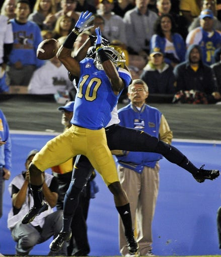 Oct 12, 2013; Pasadena, CA, USA; UCLA Bruins cornerback Fabian Moreau (10) breaks up a pass to California Golden Bears wide receiver James Grisom (85) during second quarter action at Rose Bowl. Mandatory Credit: Robert Hanashiro-USA TODAY Sports