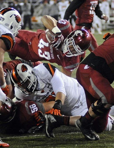 Oct 12, 2013; Pullman, WA, USA; Washington State Cougars running back Jeremiah Laufasa (43) leaps over Oregon State Beavers safety Micah Audiss (37) for a touchdown during the second half at Martin Stadium. Mandatory Credit: James Snook-USA TODAY Sports