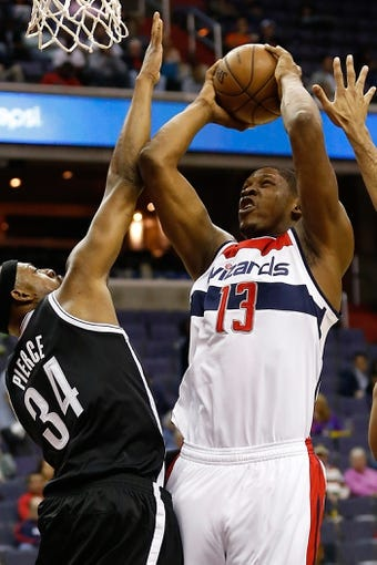 Oct 8, 2013; Washington, DC, USA; Washington Wizards power forward Kevin Seraphin (13) shoots the ball over Brooklyn Nets small forward Paul Pierce (34) at Verizon Center. Mandatory Credit: Geoff Burke-USA TODAY Sports