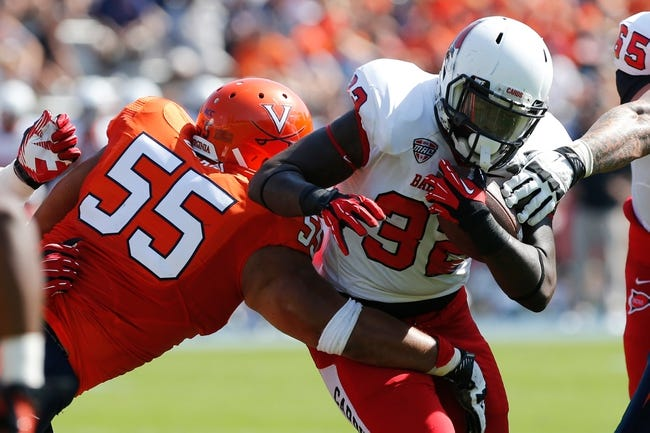 Oct 5, 2013; Charlottesville, VA, USA; Ball State Cardinals running back Jahwan Edwards (32) carries the ball as Virginia Cavaliers defensive tackle David Dean (55) attempts the tackle at Scott Stadium. Mandatory Credit: Geoff Burke-USA TODAY Sports