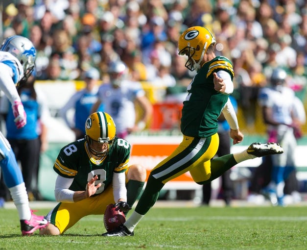 Oct 6, 2013; Green Bay, WI, USA; Green Bay Packers kicker Mason Crosby (2) kicks a field goal as punter Tim Masthay (8) holds the ball during the game against the Detroit Lions at Lambeau Field.  Green Bay won 22-9.  Mandatory Credit: Jeff Hanisch-USA TODAY Sports