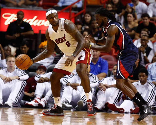 Oct 7, 2013; Miami, FL, USA; Miami Heat small forward LeBron James (6) dribbles the ball as Atlanta Hawks small forward DeMarre Carroll (5) defends in the first quarter at American Airlines Arena. Mandatory Credit: Robert Mayer-USA TODAY Sports