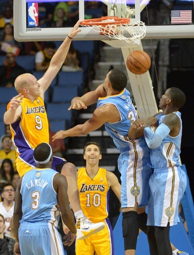 Oct 8, 2013; Ontario, CA, USA; Los Angeles Lakers center Chris Kaman (9) dunks the ball as Denver Nuggets center JaVale McGee (34) and forward Quincy Miller (30) defend at Citizens Business Bank Arena. The Lakers defeated the Nuggets90-88. Mandatory Credit: Kirby Lee-USA TODAY Sports