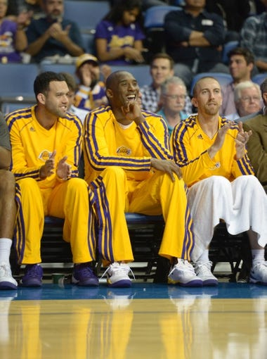 Oct 8, 2013; Ontario, CA, USA; Los Angeles Lakers guards Jordan Farmar (left), Kobe Bryant (center) and Steve Blake react during the game against the Denver Nuggets at Citizens Business Bank Arena. Mandatory Credit: Kirby Lee-USA TODAY Sports