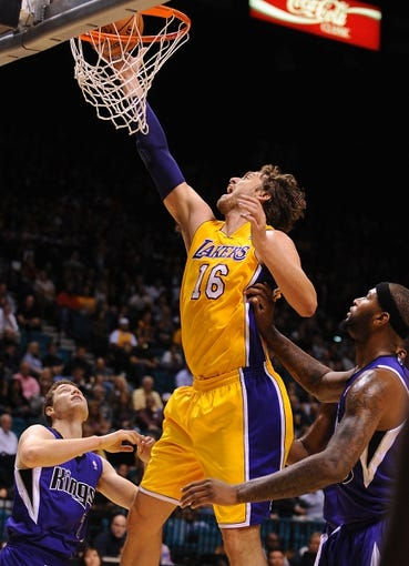 Oct 10, 2013; Las Vegas, NV, USA; Los Angeles Lakers center Pau Gasol (16) tips in a rebound over Sacramento Kings guard Jimmer Fredette (7) and center DeMarcus Cousins (15) during an NBA preseason game at MGM Grand Arena. The Kings won the game 104-86. Mandatory Credit: Stephen R. Sylvanie-USA TODAY Sports