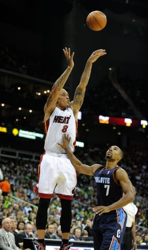 Oct 11, 2013; Kansas City, MO, USA; Miami Heat small forward Michael Beasley (8) shoots against Charlotte Bobcats point guard Ramon Sessions (7) in the second half at Sprint Center. Miami won 86-75. Mandatory Credit: John Rieger-USA TODAY Sports