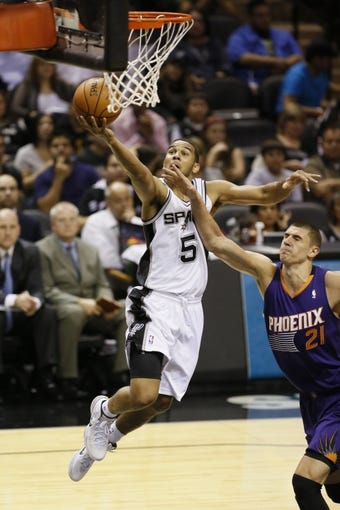 Oct 13, 2013; San Antonio, TX, USA; San Antonio Spurs guard Cory Joseph (5) drives to the basket past Phoenix Suns center Alex Len (21) during the first half at AT&T Center. Mandatory Credit: Soobum Im-USA TODAY Sports