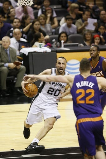 Oct 13, 2013; San Antonio, TX, USA; San Antonio Spurs guard Manu Ginobili (20) drives to the basket as Phoenix Suns  forward Miles Plumlee (22) defends during the first half at AT&T Center. Mandatory Credit: Soobum Im-USA TODAY Sports