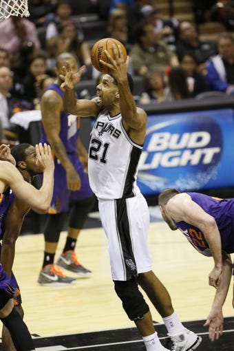 Oct 13, 2013; San Antonio, TX, USA; San Antonio Spurs forward Tim Duncan (21) drives to the basket past Phoenix Suns  forward Miles Plumlee (22) during the first half at AT&T Center. Mandatory Credit: Soobum Im-USA TODAY Sports
