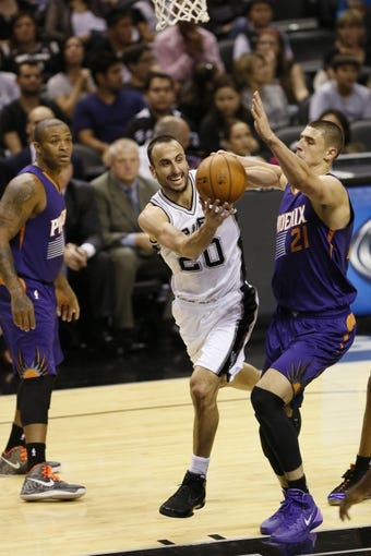 Oct 13, 2013; San Antonio, TX, USA; San Antonio Spurs guard Manu Ginobili (20) passes the ball under the basket against Phoenix Suns  center Alex Len (21) during the first half at AT&T Center. Mandatory Credit: Soobum Im-USA TODAY Sports