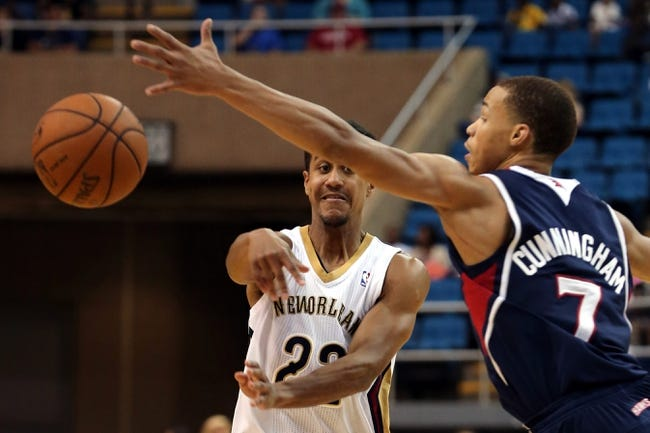 Oct 13, 2013; Biloxi, MS, USA; New Orleans Pelicans point guard Brian Roberts (22) passes under the hand of Atlanta Hawks shooting guard Jared Cunningham (7) during the second half of their game at the Mississippi Coast Coliseum. The Pelicans won 105-73. Mandatory Credit: Chuck Cook-USA TODAY Sports
