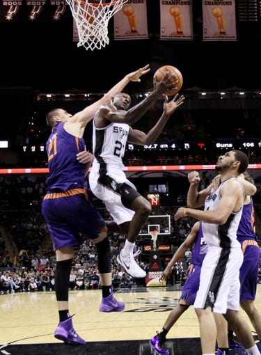 Oct 13, 2013; San Antonio, TX, USA; San Antonio Spurs guard Courtney Fells (27) drives to the basket under pressure from Phoenix Suns  center Alex Len (21) during the second half at AT&T Center. The Suns won 106-99. Mandatory Credit: Soobum Im-USA TODAY Sports