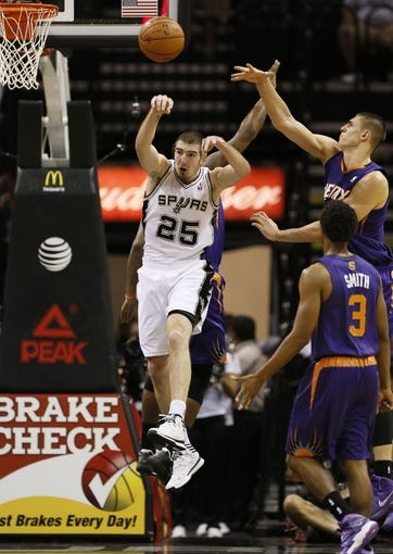 Oct 13, 2013; San Antonio, TX, USA; San Antonio Spurs guard Nando De Colo (25) passes the ball against the Phoenix Suns during the second half at AT&T Center. The Suns won 106-99. Mandatory Credit: Soobum Im-USA TODAY Sports