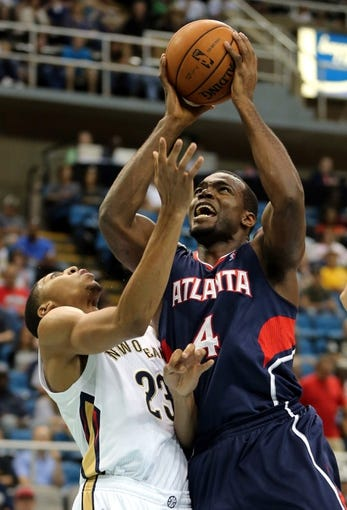 Oct 13, 2013; Biloxi, MS, USA; Atlanta Hawks power forward Paul Millsap (4) drive past New Orleans Pelicans power forward Anthony Davis (23) to the basket during the first half of their game at the Mississippi Coast Coliseum. Mandatory Credit: Chuck Cook-USA TODAY Sports