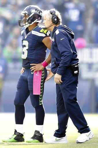 Oct 13, 2013; Seattle, WA, USA; Seattle Seahawks head coach Pete Carroll talks with Seattle Seahawks quarterback Russell Wilson (3) during a second quarter timeout against the Tennessee Titans at CenturyLink Field. Mandatory Credit: Joe Nicholson-USA TODAY Sports