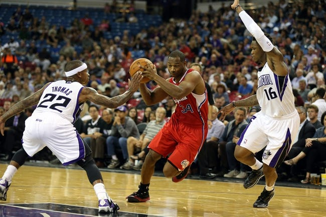 Oct 14, 2013; Sacramento, CA, USA; Los Angeles Clippers shooting guard Willie Green (34) drives in between Sacramento Kings point guard Isaiah Thomas (22) and shooting guard Ben McLemore (16) during the second quarter at Sleep Train Arena. Mandatory Credit: Kelley L Cox-USA TODAY Sports