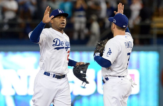 October 14, 2013; Los Angeles, CA, USA; Los Angeles Dodgers left fielder Carl Crawford (25) and shortstop Nick Punto (7) celebrate the 3-0 victory against the St. Louis Cardinals in game three of the National League Championship Series baseball game at Dodger Stadium. Mandatory Credit: Jayne Kamin-Oncea-USA TODAY Sports