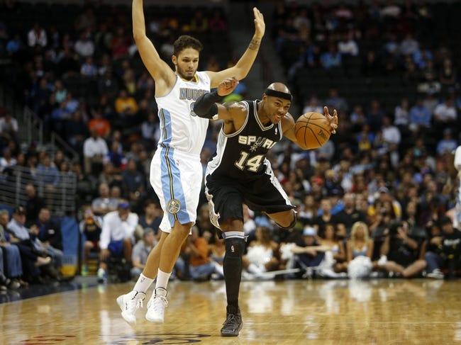 Oct 14, 2013; Denver, CO, USA; San Antonio Spurs forward Corey Maggette (14) takes the ball up the court against Denver Nuggets guard Evan Fournier (94) during the second half at Pepsi Center. The Nuggets won 98-94. Mandatory Credit: Chris Humphreys-USA TODAY Sports