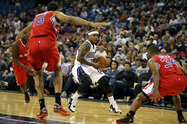 Oct 14, 2013; Sacramento, CA, USA; Sacramento Kings point guard Isaiah Thomas (22) drives in between Los Angeles Clippers center Ryan Hollins (15) and shooting guard Willie Green (34) during the third quarter at Sleep Train Arena. The Sacramento Kings defeated the Los Angeles Clippers 99-88. Mandatory Credit: Kelley L Cox-USA TODAY Sports