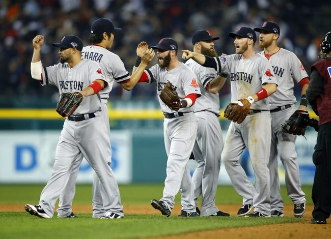Oct 15, 2013; Detroit, MI, USA;  Boston Red Sox second baseman Dustin Pedroia (center) celebrates with teammates after defeating the Detroit Tigers 1-0 in game three of the American League Championship Series baseball game at Comerica Park. Mandatory Credit: Rick Osentoski-USA TODAY Sports