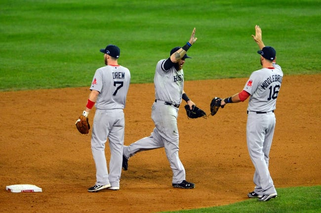 Oct 15, 2013; Detroit, MI, USA; Boston Red Sox left fielder Jonny Gomes (center) high fives third baseman Will Middlebrooks (16) after defeating the Detroit Tigers in game three of the American League Championship Series baseball game at Comerica Park. Boston won 1-0. Mandatory Credit: Andrew Weber-USA TODAY Sports