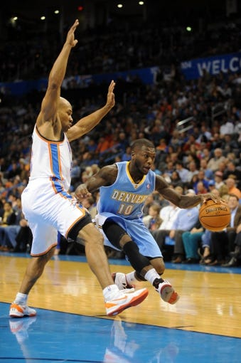 Oct 15, 2013; Oklahoma City, OK, USA; Denver Nuggets point guard Nate Robinson (10) handles the ball against Oklahoma City Thunder point guard Derek Fisher (6) during the second quarter at Chesapeake Energy Arena. Mandatory Credit: Mark D. Smith-USA TODAY Sports