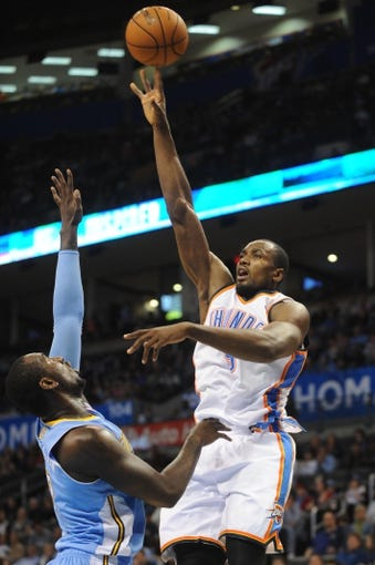 Oct 15, 2013; Oklahoma City, OK, USA; Oklahoma City Thunder power forward Serge Ibaka (9) attempts a shot against Denver Nuggets power forward J.J. Hickson (7) during the third quarter at Chesapeake Energy Arena. Mandatory Credit: Mark D. Smith-USA TODAY Sports