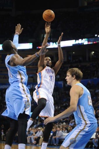 Oct 15, 2013; Oklahoma City, OK, USA; Oklahoma City Thunder small forward Kevin Durant (35) attempts a shot against Denver Nuggets center Timofey Mozgov (25) and Nuggets small forward Quincy Miller (30) during the third quarter at Chesapeake Energy Arena. Mandatory Credit: Mark D. Smith-USA TODAY Sports