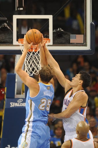 Oct 15, 2013; Oklahoma City, OK, USA; Denver Nuggets center Timofey Mozgov (25) attempts a shot against Oklahoma City Thunder center Steven Adams (12) during the fourth quarter at Chesapeake Energy Arena. Mandatory Credit: Mark D. Smith-USA TODAY Sports