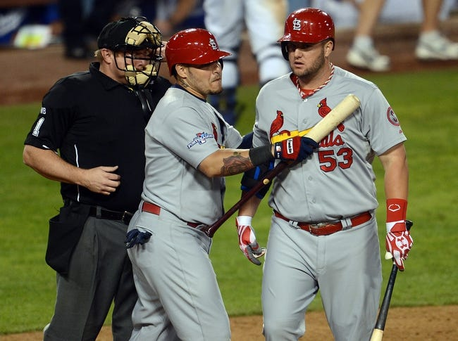 October 15, 2013; Los Angeles, CA, USA; St. Louis Cardinals first baseman Matt Adams (53) is held back by catcher Yadier Molina (4) after he argues a strikeout call to umpire Bruce Dreckman in the ninth inning against the Los Angeles Dodgers  in game four of the National League Championship Series baseball game at Dodger Stadium. Mandatory Credit: Jayne Kamin-Oncea-USA TODAY Sports