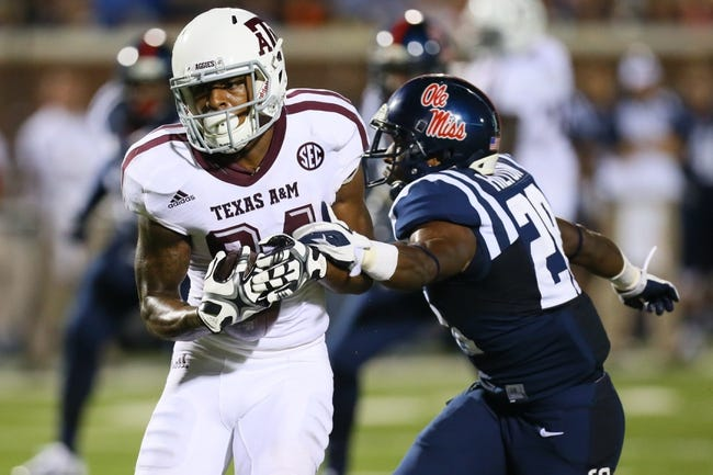 Oct 12, 2013; Oxford, MS, USA; Texas A&M Aggies wide receiver Malcome Kennedy (84) advances the ball against Mississippi Rebels defensive back Mike Hilton (28) during the game at Vaught-Hemingway Stadium. Texas A&M Aggies defeated the Mississippi Rebels 41-48.  Mandatory Credit: Spruce Derden-USA TODAY Sports
