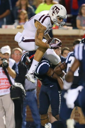 Oct 12, 2013; Oxford, MS, USA; Texas A&M Aggies wide receiver Mike Evans (13) jumps over Mississippi Rebels defensive back Tony Conner (12) during the game at Vaught-Hemingway Stadium. Texas A&M Aggies defeated the Mississippi Rebels 41-48.  Mandatory Credit: Spruce Derden-USA TODAY Sports