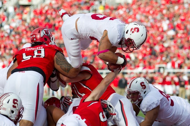 Oct 12, 2013; Salt Lake City, UT, USA; Stanford Cardinal running back Tyler Gaffney (25) jumps over the Utah Utes defense to score a touchdown during the first half at Rice-Eccles Stadium. Utah defeated Stanford 27-21. Mandatory Credit: Russ Isabella-USA TODAY Sports