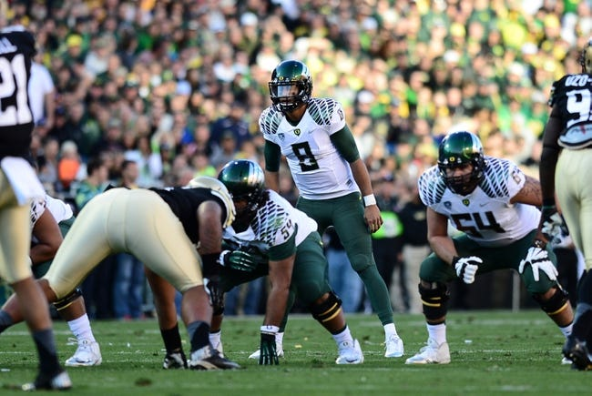 Oct 5, 2013; Boulder, CO, USA; Oregon Ducks quarterback Marcus Mariota (8) at the line of scrimmage in the second quarter against the Colorado Buffaloes at Folsom Field. Mandatory Credit: Ron Chenoy-USA TODAY Sports