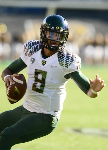 Oct 5, 2013; Boulder, CO, USA; Oregon Ducks quarterback Marcus Mariota (8) scrambles in the first quarter against the Colorado Buffaloes at Folsom Field. Mandatory Credit: Ron Chenoy-USA TODAY Sports